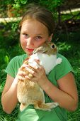stock photo of  preteen girls  - portrait of a young girl holding a bunny outside - JPG
