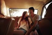 Постер, плакат: Affectionate Young Couple In Rear Seat Of A Car
