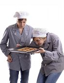 Two Young Female Cooks Inspecting Cookies