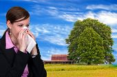stock photo of hay fever  - A beautiful woman with a cold hay fever or allergies blowing her nose - JPG