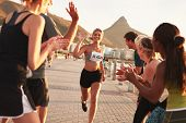 Постер, плакат: Group Of Spectators Cheering Runners At Finish Line