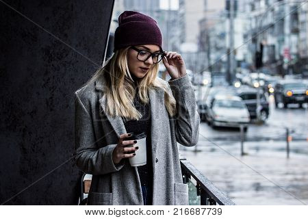 d772011b2920 Woman with perfect city style. Portrait of stylish hipster girl in coat  holding glasses and