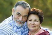 stock photo of elderly couple  - Happy elderly couple embracing in the park - JPG