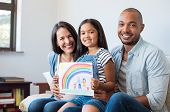 Smiling daughter showing painting of family with parents and beautiful rainbow. Happy child showing  poster