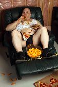 stock photo of beer-belly  - Lazy overweight male sitting on a couch watching television - JPG