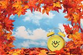 picture of daylight-saving  - Fall leaf border with clock sky background - JPG