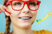 Girl With Teeth Braces Using Interdental And Traditional Brush poster