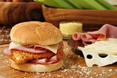 Freshly prepared chicken cordon bleu sandwich on wood cutting board with breadcrumbs.  Swiss cheese,