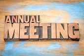annual meeting word abstract in letterpress wood type against grunge wooden background poster