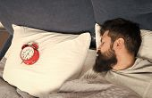 Man Bearded Hipster Sleepy Face In Bed With Alarm Clock. Problem With Early Morning Awakening. Get U poster