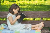Little Girl Holds Book In Her Hands. Reading The Book In In Outdoors. The Girl On Sitting On A Bench poster