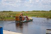 foto of airboat  - People on an air boat going for a ride in the Everglades - JPG