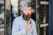 Bearded Man Smoking Vape. Man With Beard Breathe Out Smoke. Clouds Of Flavored Smoke. Smoking Electr poster