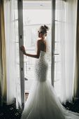 Stylish Bride Opening Window Balcony In Soft Light In Hotel Room. Back Of Gorgeous Sensual Bride In poster