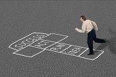 stock photo of hopscotch  - Businessman playing hopscotch towards success taking necessary steps - JPG