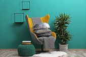 Armchair With Plaid And Pillows In Cozy Room Interior poster