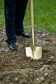 foto of shovel  - A gold shovel digs into the dirt at a groundbreaking ceremony - JPG