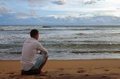 Young Man In A White Shirt Meets The Sunset On A Tropical Ocean Beach poster