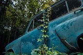 Abandoned Rusty Car In Junkyard. Forgotten Discarded Rusty Old Blue Car In Scrapyard poster