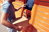 Man Using Automated Self Service Post Terminal Machine Or Locker To Deposit The Parcel For Storage poster