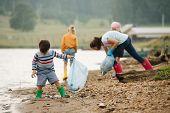 Little Boy Collecting Garbage With Group Of Kids Along The River. Eco Tourism. Environmental Polluti poster