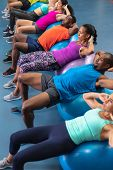 High angle of diverse fit people exercising on exercise ball in fitness center. Bright modern gym wi poster