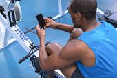 High angle of African-american fit man using mobile phone while exercising on rowing machine in fitn poster