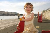 image of lurch  - A playful little girl is rocking on the playground - JPG