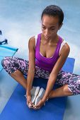 Close-up of African-american fit woman performing yoga on a exercise mat in fitness center. Bright m poster