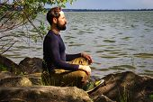 A Bearded Man Is Meditating By The River Emotional Meditating Lifestyle. Introspection Relaxing poster