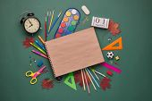 Blank writing-book and stationery accessories: pencils, pens, other office supplies on green backgro poster