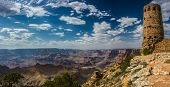 stock photo of cloud formation  - Panorama of the grand canyon with a blue sky and white clouds and the Desert View watchtower to the right of the image - JPG