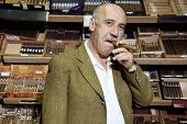 Portrait of middle-aged tobacco shop owner smoking cigar in store
