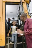stock photo of bus driver  - Little girl looking at man while getting down from school bus with driver sitting in background - JPG