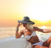 stock photo of bimbo  - Young sexy woman in white bikini enjoying the sunset on her private yacht - JPG