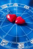 two red hearts over blue astrology background