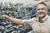 Portrait of a happy middle-aged salesperson holding metallic equipment in hardware store