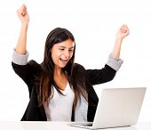 Successful woman with arms up working on a laptop