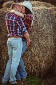 stock photo of cowgirl  - young adult couple kissing near hay. This image has attached release.