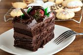 picture of fancy cake  - Italian cookies and a decadent slice of chocolate cake with iced flowers and chocolate covered strawberries on a plate with a fork - JPG