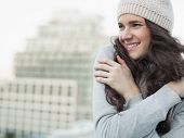 stock photo of shivering  - Cheerful pretty young brunette shivering outside on a cloudy day - JPG