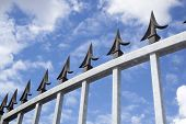 image of spike  - Angled Closeup detailed view of galvanised security gate and black decorative spikes against sky and cloud background - JPG