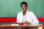Portrait of happy African American female teacher sitting with binder at desk in classroom