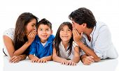 Happy family telling a secret to the ear - isolated over white
