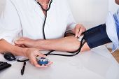 foto of sphygmomanometer  - Attractive young female doctor or nurse taking a male patients blood pressure using a sphygmomanometer - JPG