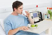 pic of hospital gown  - Young male patient drinking water while having meal in hospital - JPG