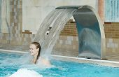 foto of water jet  - Girl in a swimming pool standing under a jet of water from a curved poolside water feature - JPG