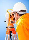 foto of theodolite  - Portrait of Senior land surveyor working with theodolite at construction site - JPG