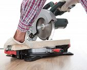 foto of sawing  - Worker cutting timber using circular electric saw - JPG