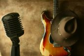 stock photo of stratocaster  - Vintage microphone and vintage sunburst strat with a cowboy hat - JPG